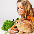 Pretty cheerful girl feeding a rabbit - Stock Photo