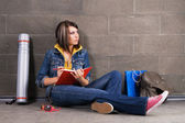 ładny studenta przy ścianie, pisanie na notebooka — Zdjęcie stockowe