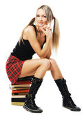 Lovely student girl sitting on a stack of books — Stock Photo