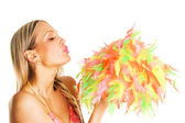 Pretty girl blowing on colorful feathers — Stock Photo