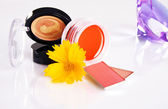 Cosmetici con un fiore giallo e cristallo blu su sfondo — Foto Stock