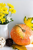 Pumpkin with a bunch of flowers — Stock Photo