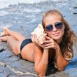Girl with a seashell on the sea. — Stock Photo #7034443