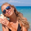 Girl with a seashell on the sea. — Stock Photo #7034583