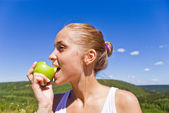 Girl eating an apple. — Stock Photo