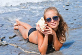 Girl with a seashell on the sea. — Stock Photo