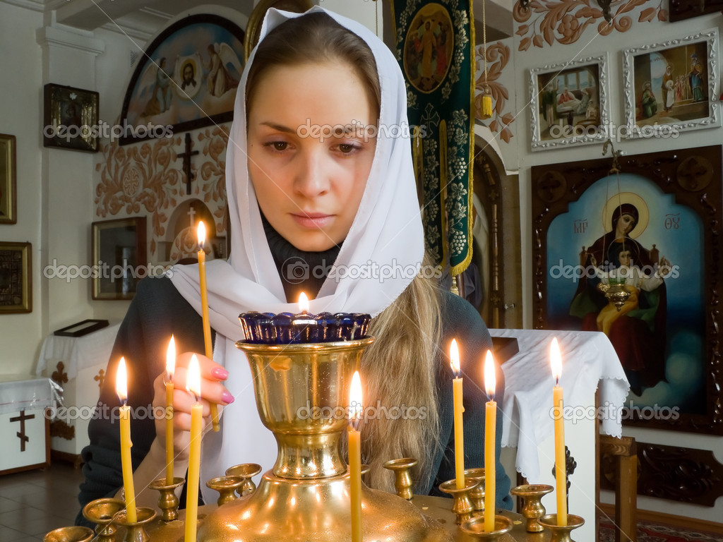 Girl with a candle in the Orthodox Church.  Stock Photo #7035582