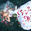 Bride lying on the grass and rose petals — Stock Photo