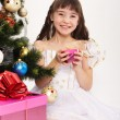 Little laughing girl opening christmas present — Stock Photo