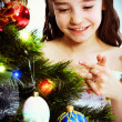 Little smiling girl under a Christmas tree — Stock Photo #7516354