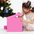 Little smiling girl opening christmas present — Stock Photo
