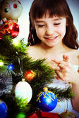 Little smiling girl under a Christmas tree — Stock Photo