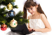 Little smiling girl looks at her laptop computer — Stock Photo