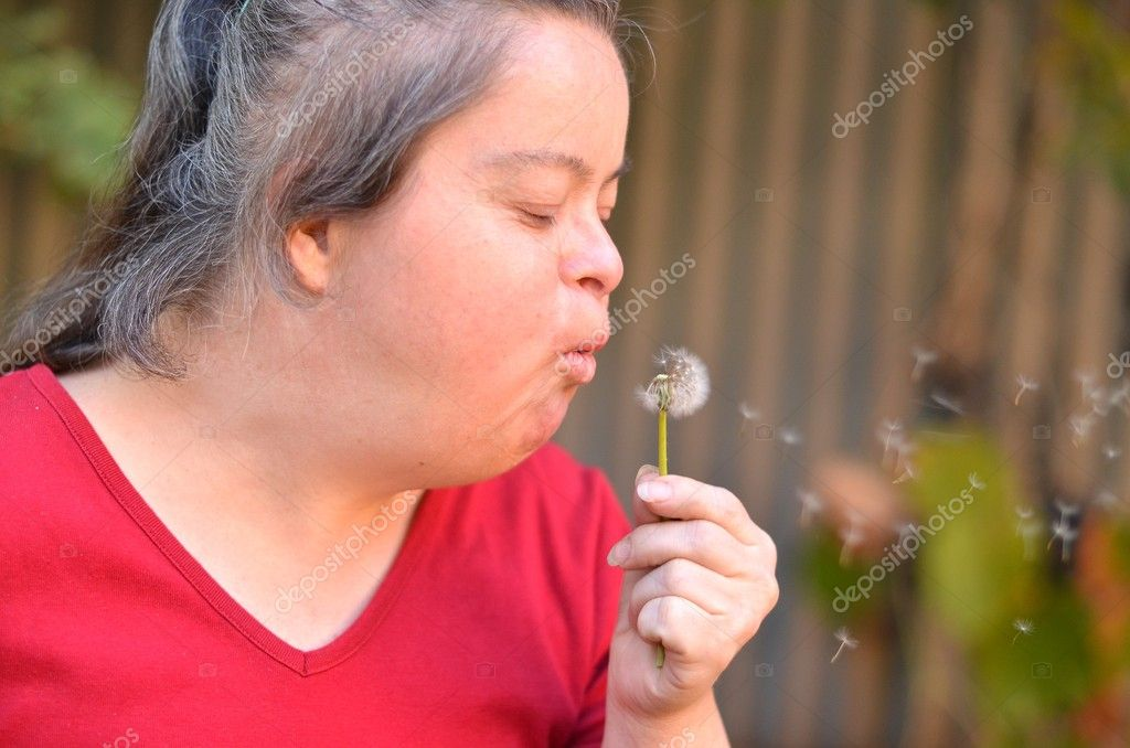Down syndrome woman blowing dandelion   Stock Photo #6986096