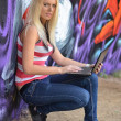 Royalty-Free Stock Photo: Girl against a wall with graffiti and laptop
