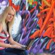 Girl against a wall with graffiti and laptop — Stock Photo #7084574