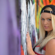 Stock Photo: Girl against a wall with graffiti