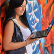 Girl against a wall with graffiti and laptop — Stock Photo