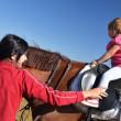 Very little girl on her black horse — Stock Photo