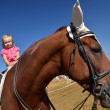 Very little girl on her black horse — Stock Photo