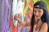 Girl against a wall with graffiti — Stock Photo