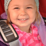 Little girl sitting in car safety seat.shot made through window pane — Stock Photo