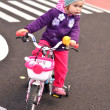 Little girl riding on her pink bike — Stock Photo