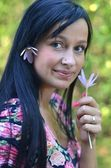 Beautiful young brunette woman with flower in her hair — Stock Photo