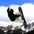 Flying snowboarder on mountains — Stock Photo