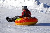 Child sledding on inner tube — Stock Photo