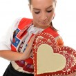 Beautiful girl shows a gingerbread heart — Stock Photo #7295725