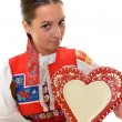 Beautiful girl shows a gingerbread heart — Stock Photo