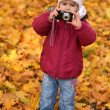 Young girl with camera in autumn park — Stock Photo #7459124