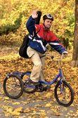 Podobizna muže downův syndrom s cyklem v podzimním parku — Stock fotografie