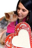 Young woman and sweet puppy with gingerbread heart — Stock Photo