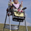 Little baby girl sitting in baby eating chair on nature — Stockfoto