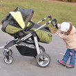 Baby pushing stroller — Stock Photo