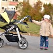 Baby pushing stroller — Stock Photo #7743344