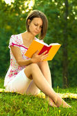 Beautiful woman immersed in a romantic book — Stock Photo