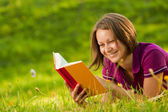Beautiful woman laughing with a book in the park — Stock Photo