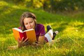 Vacker kvinna med en bok i parken — Stockfoto