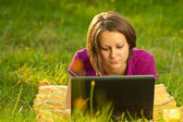 Beautiful woman with a laptop in the park — Stock Photo