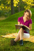 Beautiful woman writing in her diary in the park — Stock Photo