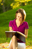 Beautiful woman writing in her diary — Stock Photo