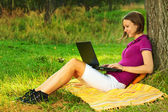 Beautiful excited woman with a laptop in the park — Stock Photo