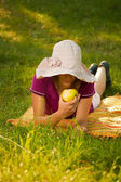 Beautiful woman eating an apple in the park — Stock Photo