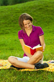 Beautiful woman enjoying a funny book, vertical — Stock Photo
