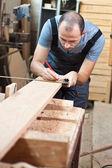 Man measuring a wood plank — Stock Photo