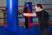Boxer punzonatura un sacchetto di sabbia con la mano posteriore — Foto Stock