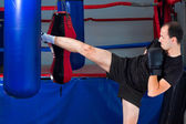 Boxer roundhouse kicking a sand bag — Stock Photo